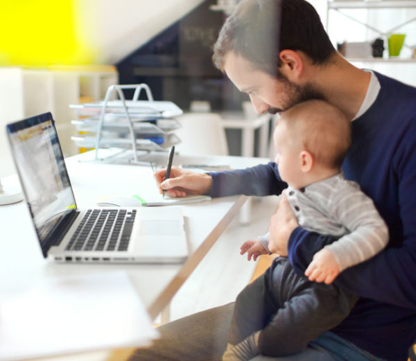 Father and Son sitting at a table doing banking work on the computer