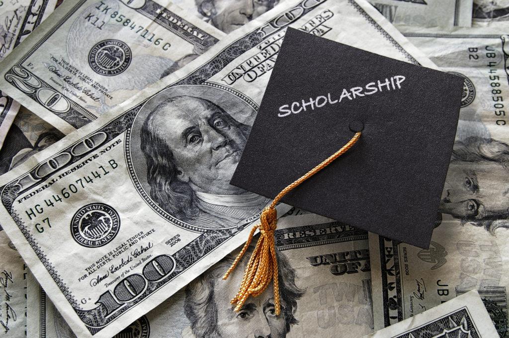Scholarship mini graduation cap on cash