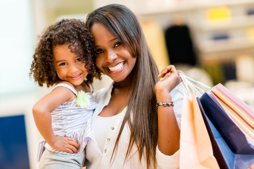 Young mom and daughter holding shopping bags