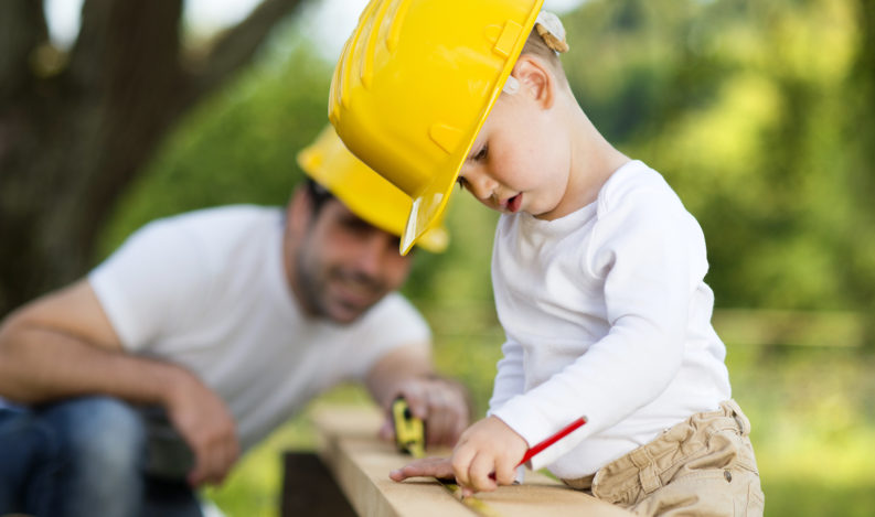 dad and young son doing home improvements together