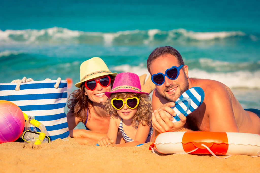 Save money on summer vacation. Family laying on the sand in front of the ocean.