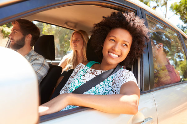 Young adults riding in a car with the focus on a pretty young girl leaning out the car window