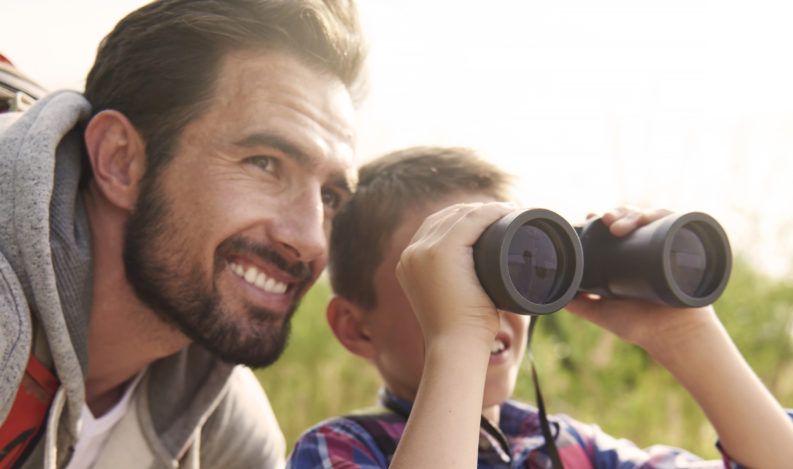 Father and son hiking in the woods and looking at wildlife through binoculars.
