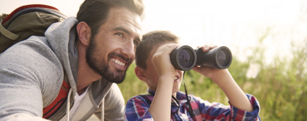 Father and son hiking in the woods and looking through binoculars.