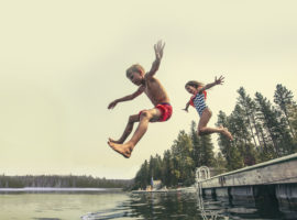 Kids jumping off pier into lake