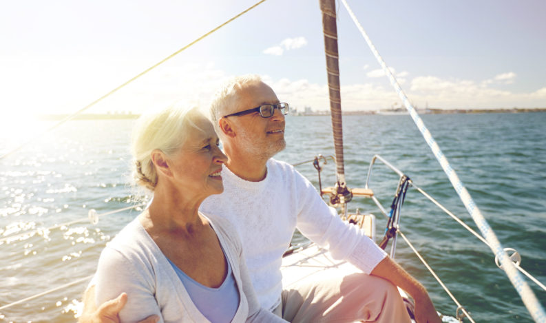 happy senior couple hugging on sail boat or yacht deck floating in sea