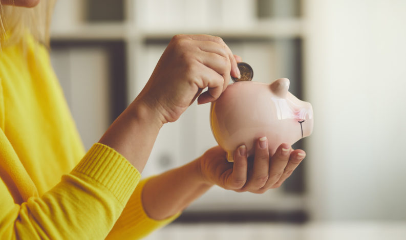 Woman inserts a coin into her savings piggy bank