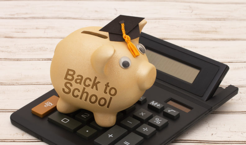 Back to School Savings, A golden piggy bank with grad cap and calculator on a wood background with text Back to School