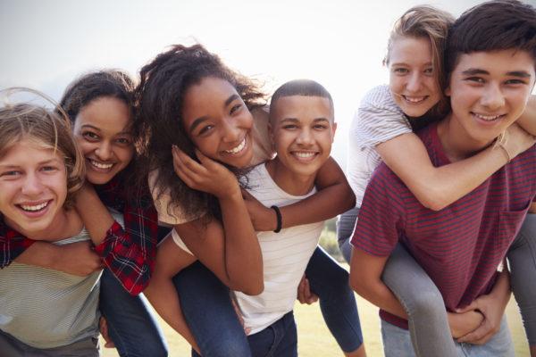 Teenage school friends having fun piggybacking outdoors