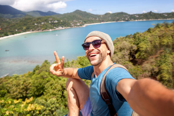 Young male hipster traveler doing selfie overlooking the tropical sea.