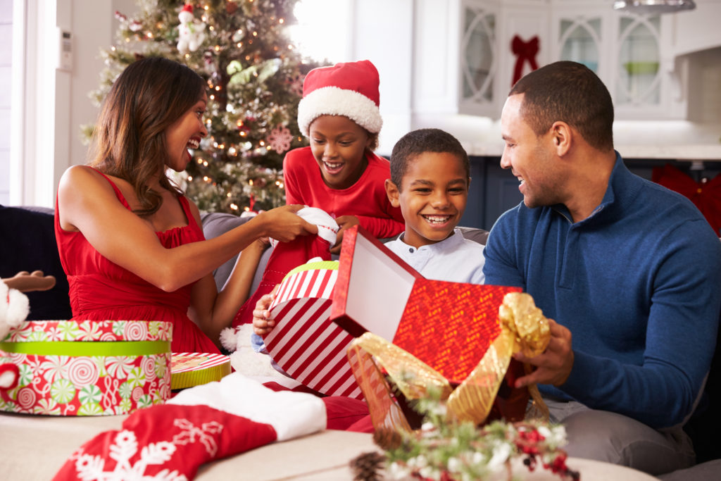 Family Opening Christmas Presents At Home Together enjoying the holidays.