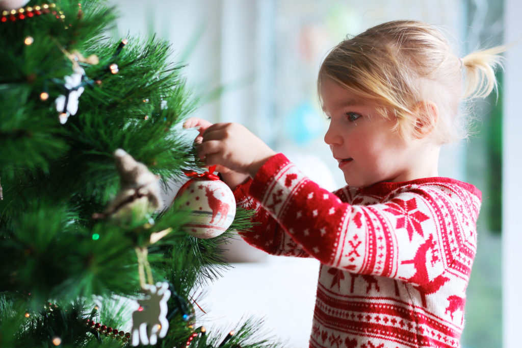Little girl decorating christmas tree with toys and baubles. Cute kid preparing home for a holiday celebration.