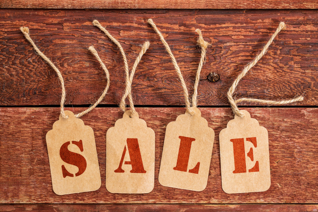 sale sign or concept - letters on price tags against rustic red painted barn wood