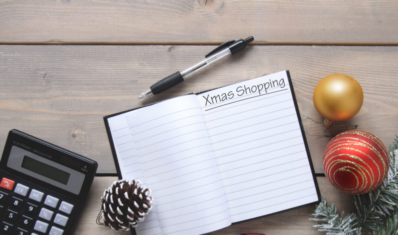 Christmas decorations around a notepad with Christmas shopping list