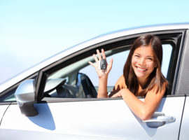 Asian car driver woman smiling showing new car keys and car.