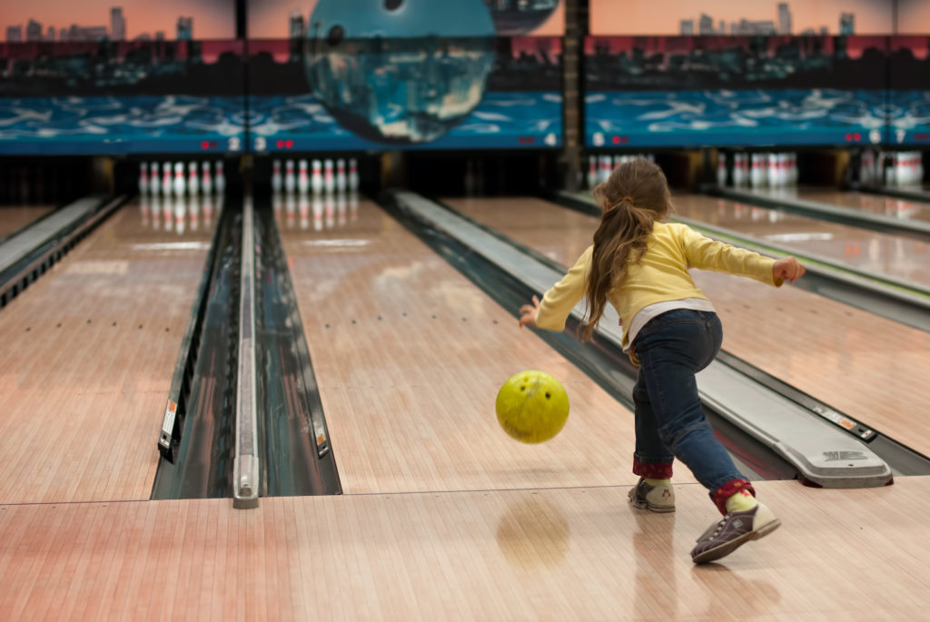 young girl playing in a bowling alley