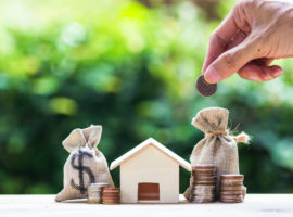 Saving money, home loan, mortgage, a property investment for future concept : A man hand putting money coin over small residence house and money bag with nature background. A sustainable investment.