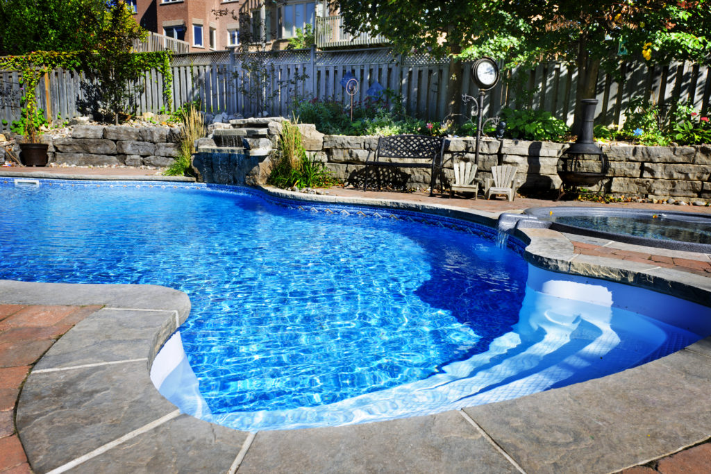 Residential inground swimming pool in backyard with waterfall and hot tub
