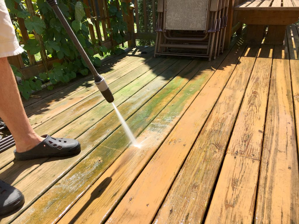 Cleaning wooden deck with pressure washer