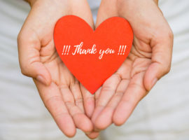 Young woman hand holding red heart paper with THANK YOU message. Thankful concept.