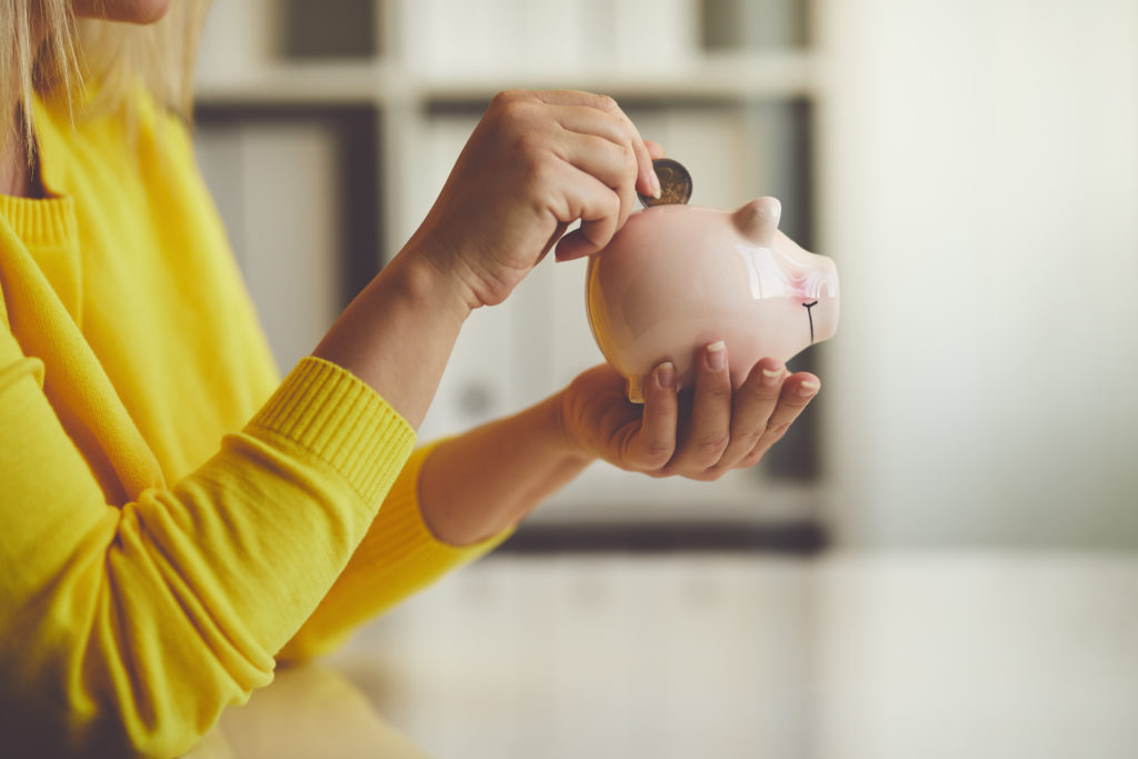 Woman inserts a coin into a piggy bank
