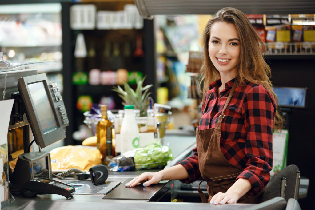 Image of cashier lady on workspace in supermarket shop. Looking at camera.