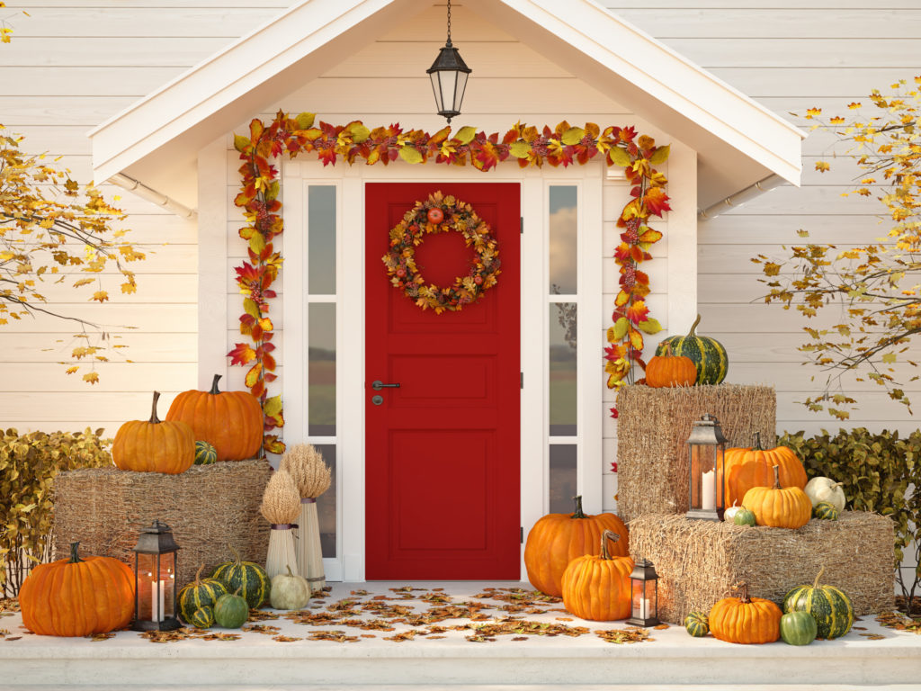 autumn decorated house with pumpkins and hay.
