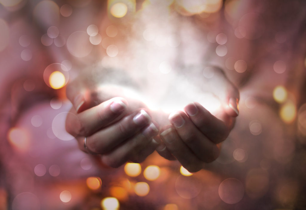 magic particles on the palms of a woman, the flow of magical energy emanating from female hands