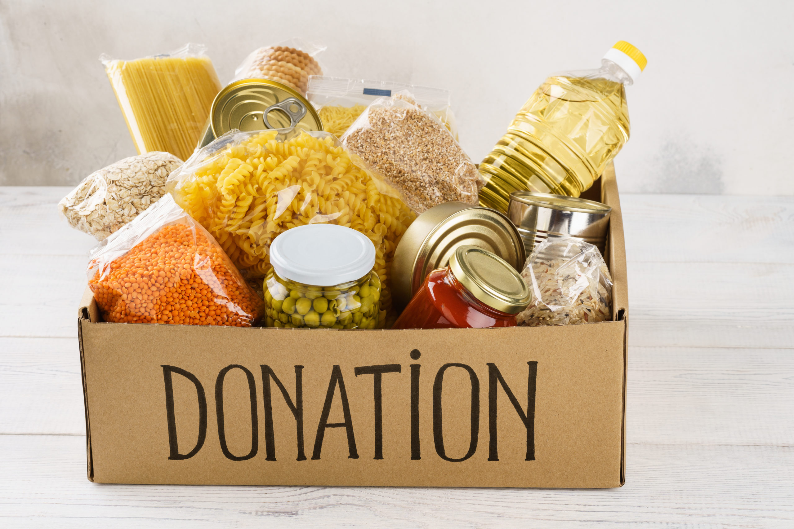 Donation box with various food. Open cardboard box with oil, canned food, cereals and pasta.