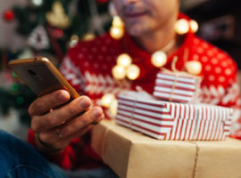 Christmas shopping online. Man buying New year presents using smartphone. Guy holding gift boxes and phone by Christmas tree