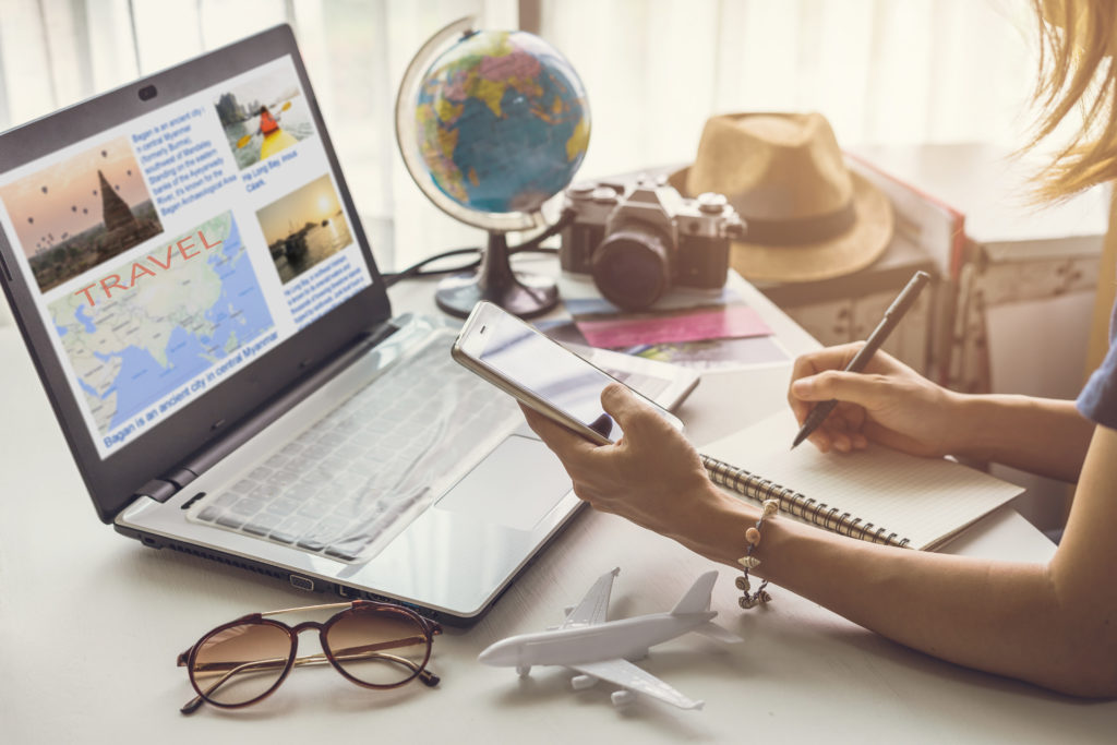 Young women planning vacation trip and searching information or booking an hotel on a smart phone and laptop