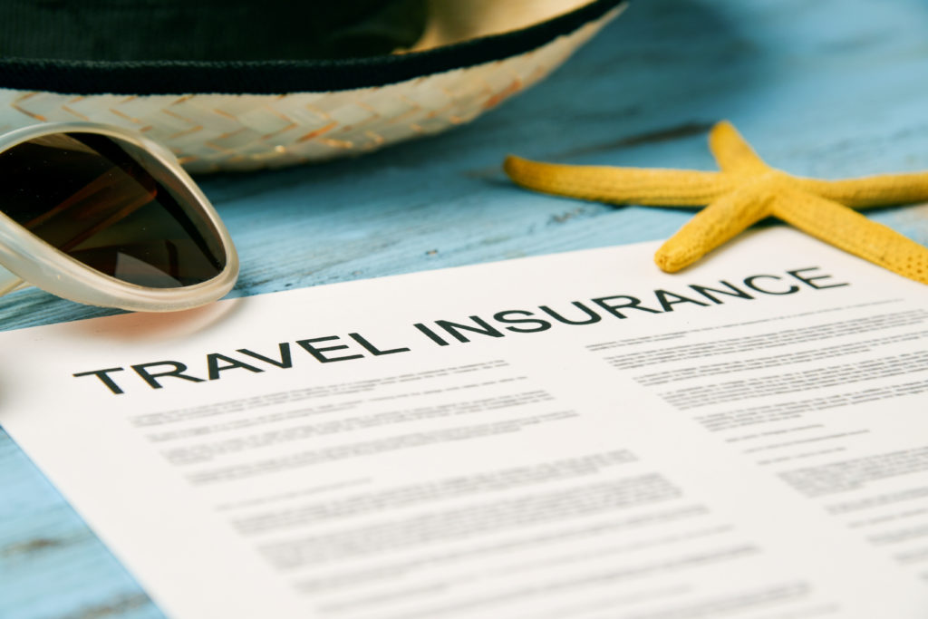 closeup of a travel insurance policy on a rustic blue wooden table, next to a pair of sunglasses, a straw hat and a starfish
