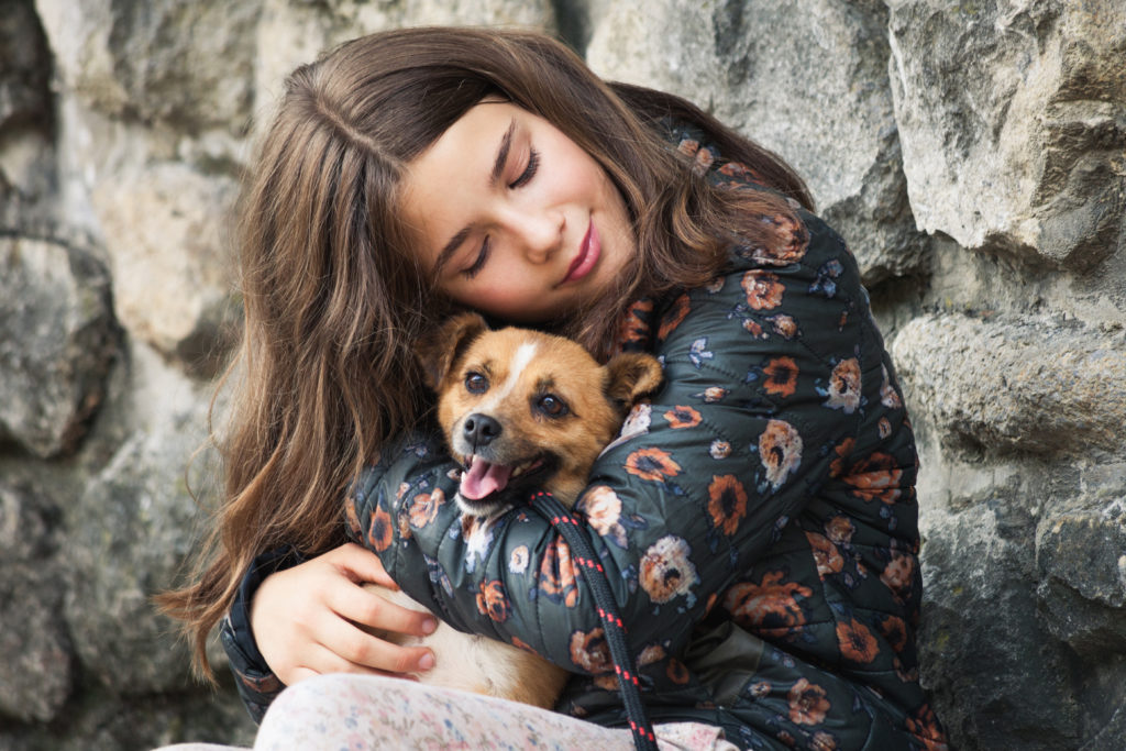 beautiful teen girl hugging her new pet adopted homeless dog from rescue shelter