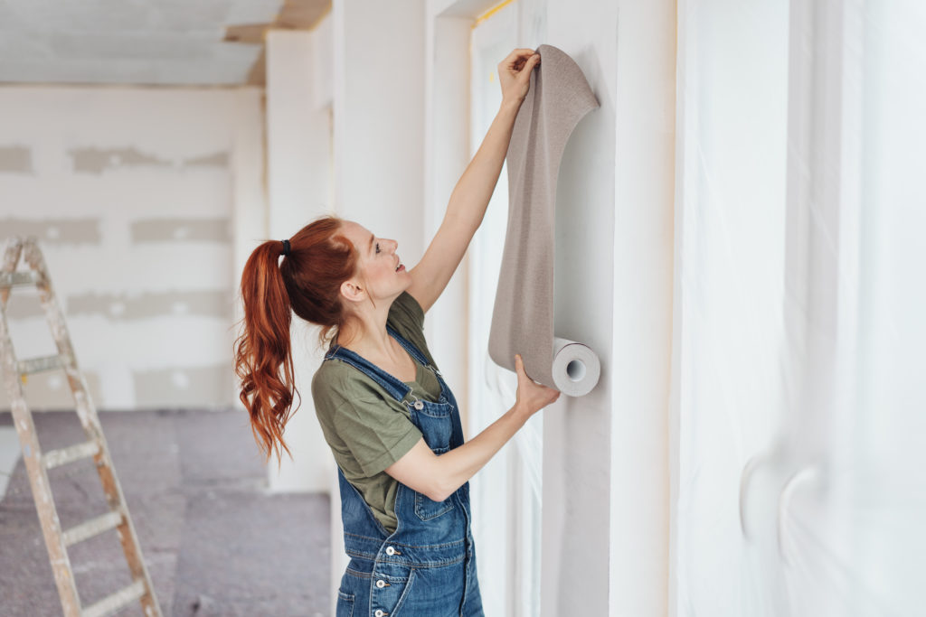 Young woman trying out new wallpaper at home holding the roll up against a newly painted white wall for visual effect