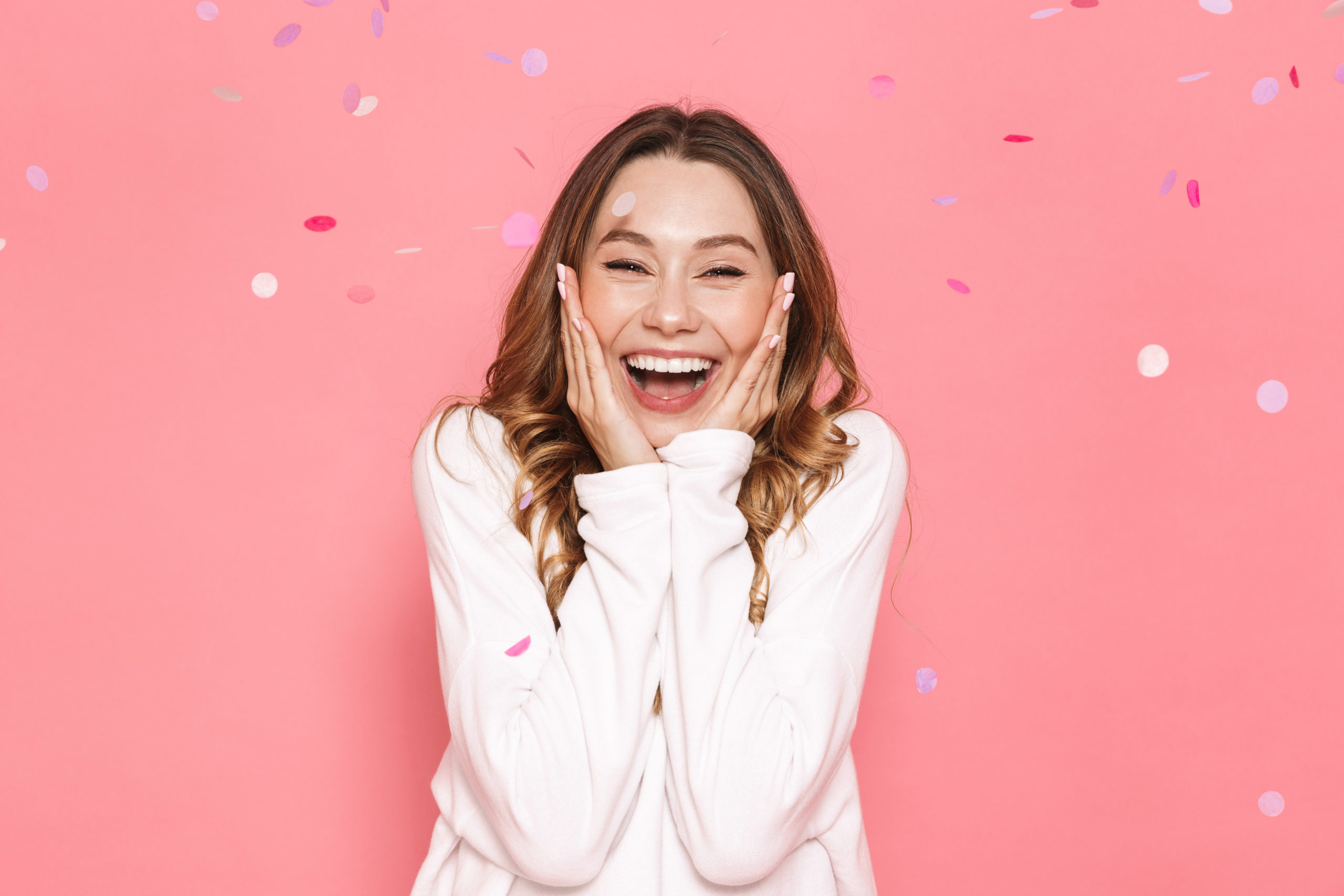 Portrait of an excited young woman celebrating under confetti shower isolated over pink background