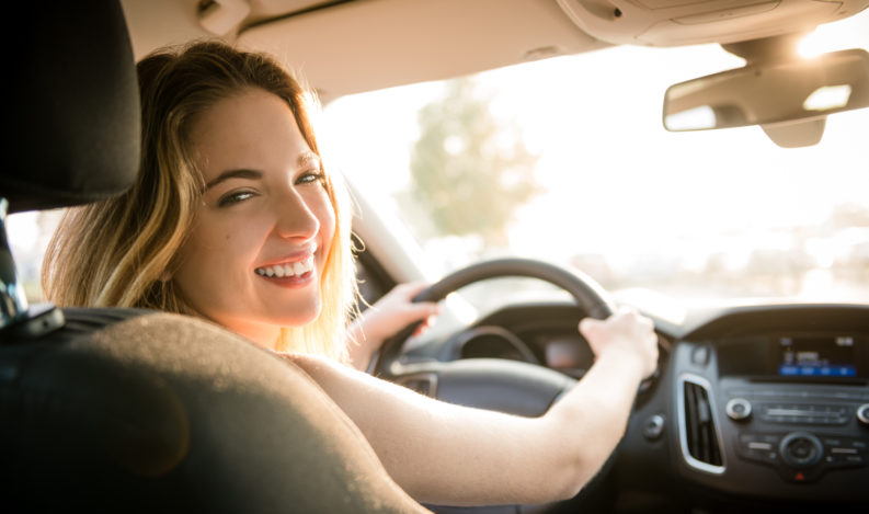 Teenage girl behind steering looking over shoulder to back seat at sunset