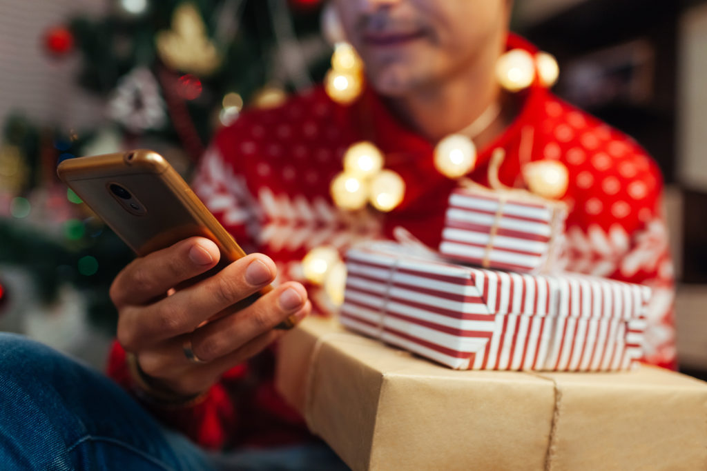 Christmas shopping online. Man buying New year presents using smartphone. Guy holding gift boxes and phone by tree