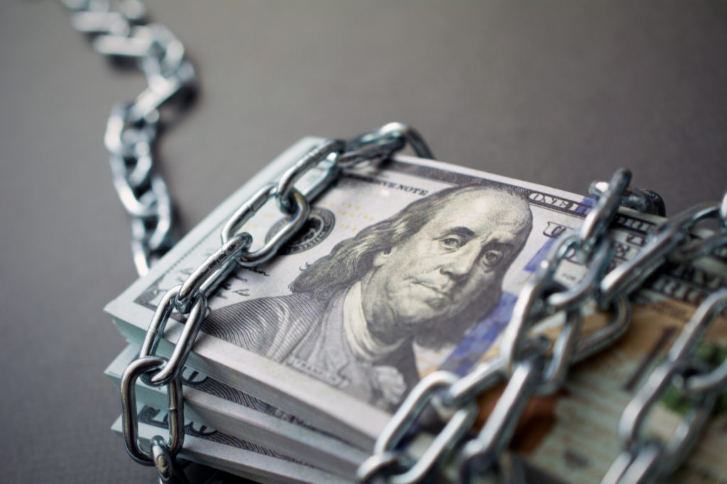 chained money, bundle of dollars tied up with a chain, the concept of credit slavery, seized assets, frozen assets. dark background, closeup