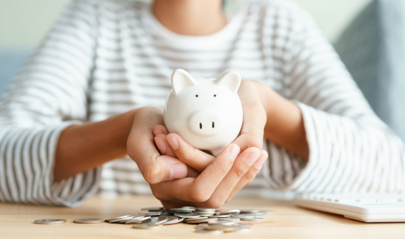 Hand of Asian young girl holding white piggy bank with two hands on the coin stack at home morning, retirement, finance and saving money for future concept