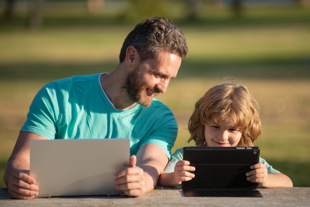 Online learning. Happy father using laptop relax with schooler son holding laptop have fun together, smiling dad and little boy child enjoy weekend with gadgets outside on nature