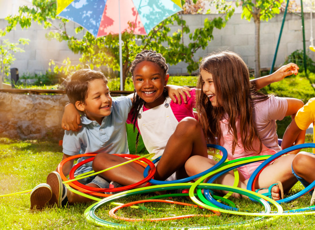 Group of thee kids boys and girls sit together with hula hoops hugging talking to each other