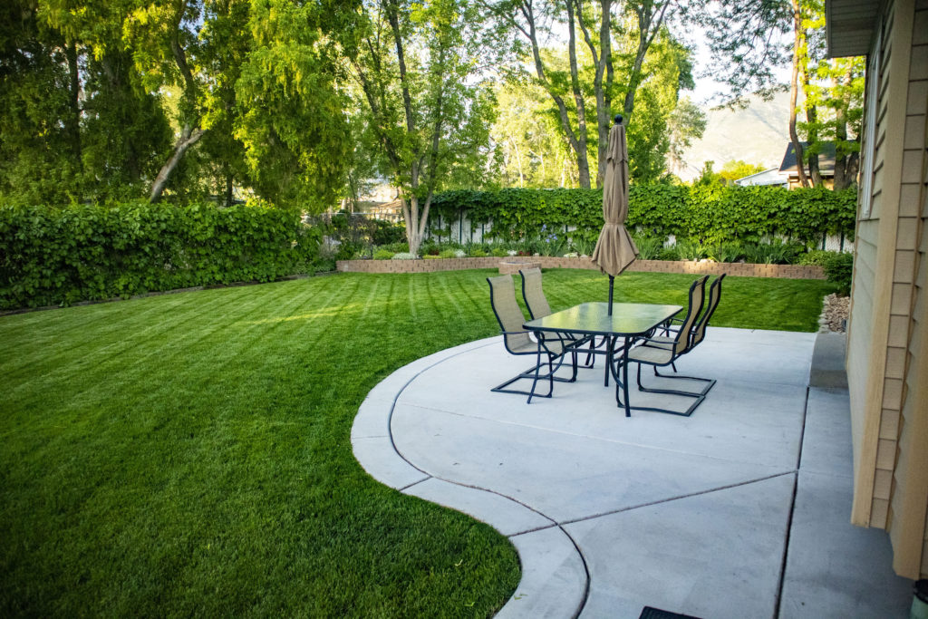 backyard patio with table and beautiful landscaping